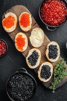 Broodjes met rode en zwarte kaviaar stokbrood, op zwarte tafel, bovenaanzicht plat lag