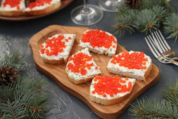 Broodjes met rode kaviaar bevinden zich op een houten bord tegen een donkere achtergrond