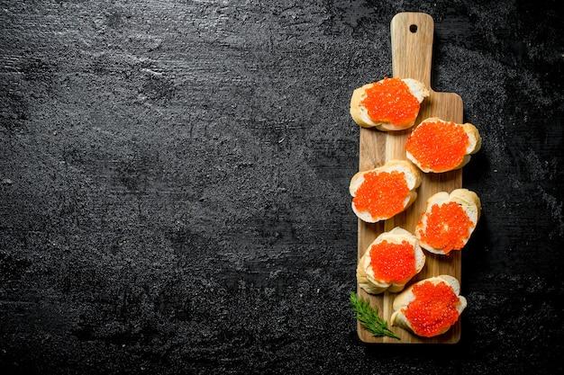 Broodjes met rode kaviaar op een snijplank met dille. op zwarte rustieke tafel