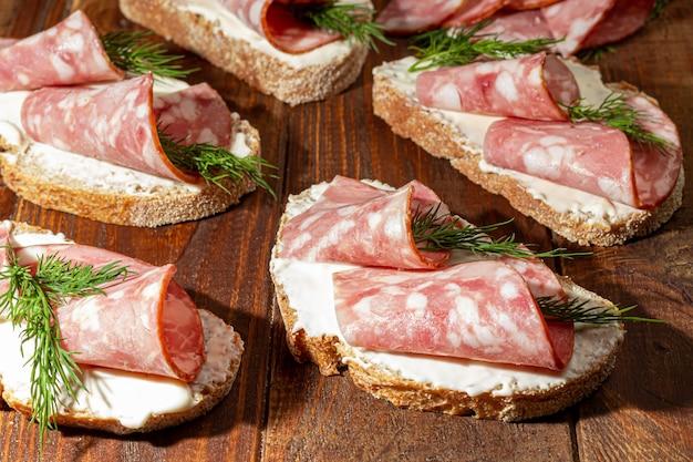 Broodjes met rookworst en roomkaas. versierd met dille kruiden. op een donkere houten achtergrond. kopieer ruimte.