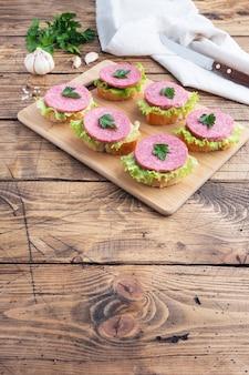 Broodjes met slablaadjes en gesneden salami worst op een houten bord. bovenaanzicht kopie ruimte