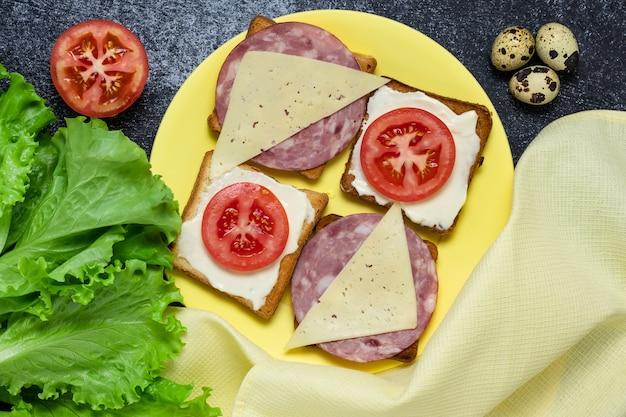Broodjes met tomaten, worst en kaas op een gele plaat