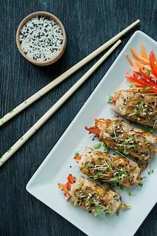 Broodjes met verse kipfilet met greens, wortelplakken, paprika op een donkere snijplank.