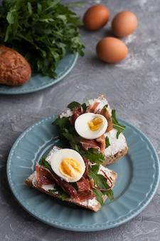 Broodjes met volkoren brood, huisgemaakte kaas, rucola, ham en ei. gezonde snack.