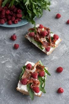 Broodjes met volkoren brood, huisgemaakte kaas, rucola, ham en sappige framboos. gezonde snack.