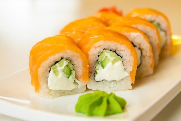 Broodjes met zalm en komkommer, kaas en wasabi op een bord