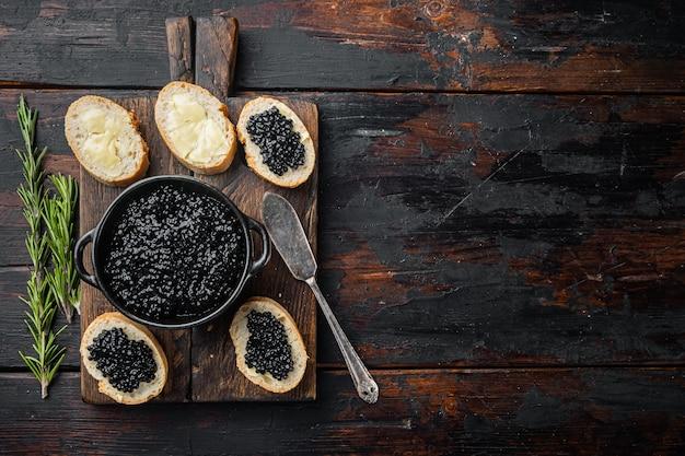 Broodjes met zwarte kaviaar, op oude donkere houten tafel tafel, bovenaanzicht plat lag