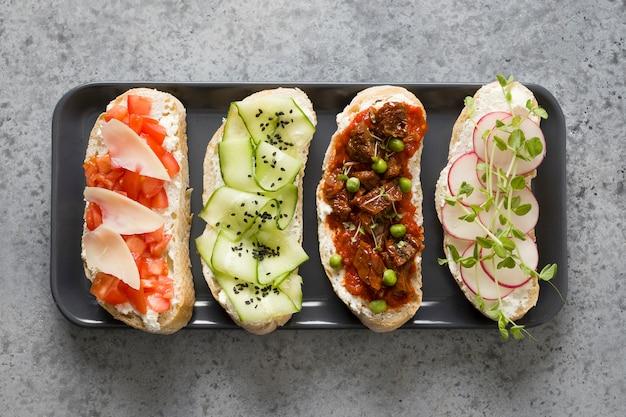 Broodjes op ciabattatoost met verse groenten, radijs, tomaten, komkommers en microgreens. uitzicht van boven.