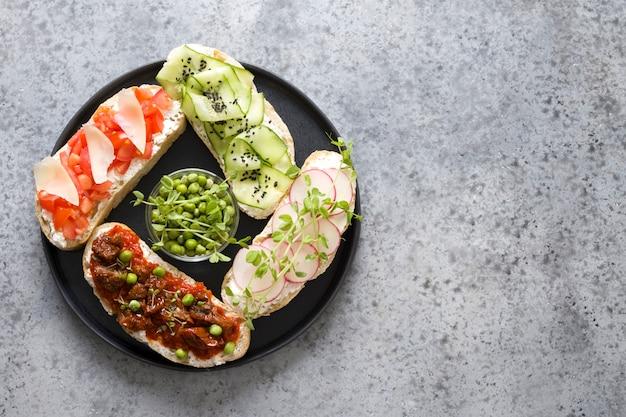 Broodjes op ciabattatoost met verse groenten, radijsjes, tomaten, komkommers en microgreens. bovenaanzicht