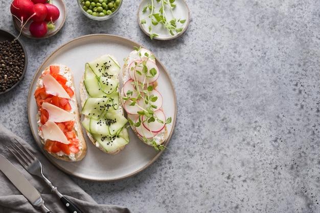 Broodjes op toast met ingrediënten, groenten, radijs, tomaten, komkommers en microgreens op grijs. uitzicht van boven.