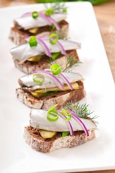 Broodjes roggebrood met haring, uien en kruiden.