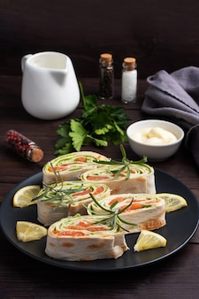 Broodjes van dun pitabroodje en rode gezouten zalm met slablaadjes op een zwarte ceramische plaat, donkere houten achtergrond hoogste mening. kopieer ruimte.