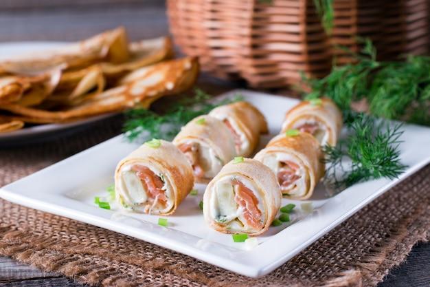 Broodjes van dunne pannenkoeken met gerookte zalm en roomkaas op plaat