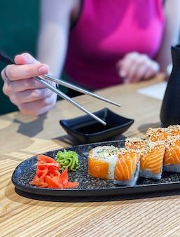 Broodjessushi eten in japans restaurant, hand met stokjes