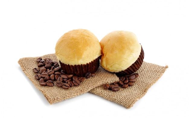Broodmuffin met koffiebonen op zak op witte muur wordt geïsoleerd die