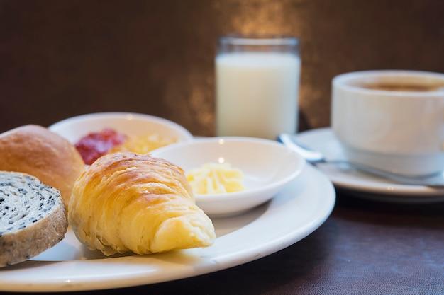 Broodontbijt met melk en koffie wordt geplaatst die