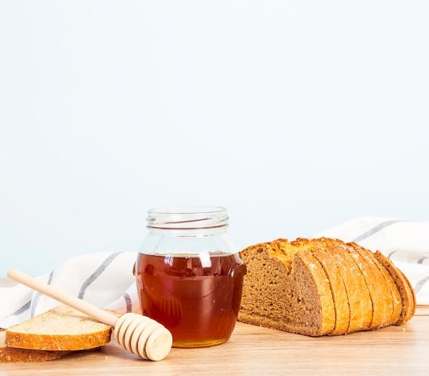 Broodplak en kruik honing voor ontbijt over houten bureau