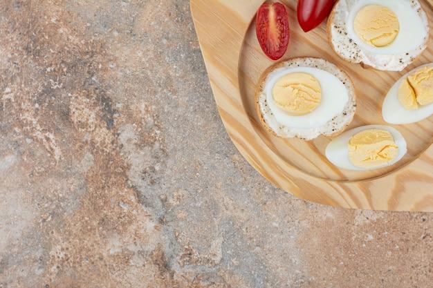 Broodplakken met gekookte eieren en tomaat op houten plaat