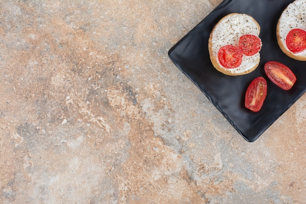 Broodplakken met room en tomaat op zwarte plaat