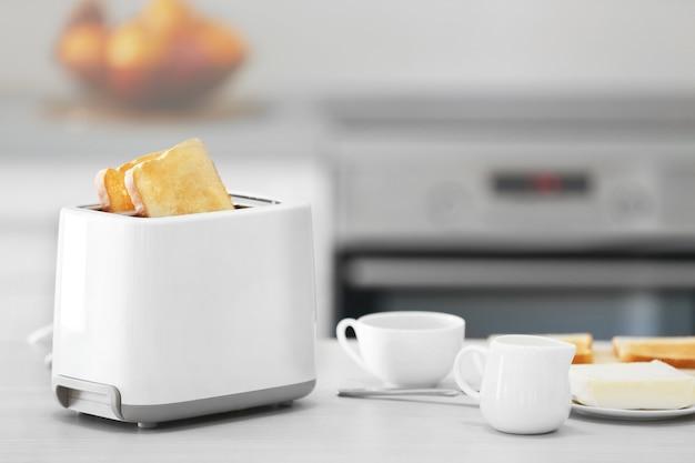 Broodrooster met gerechten op een lichte keukentafel, close-up