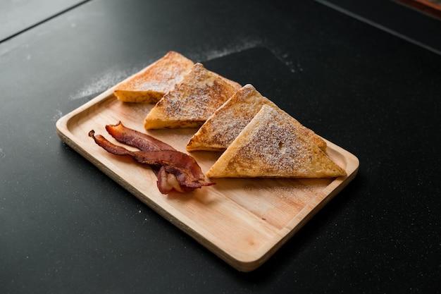 Broodrooster met spek op houten plaat