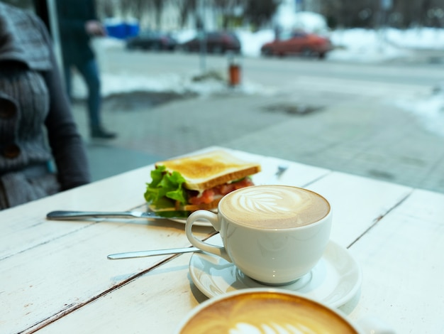 Broodsandwich met ham, kaas, kerstomaatjes, komkommer en sla en espressokoffie als ontbijt. selectieve aandacht.