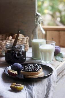 Broodtoast met pruimenjam, geserveerd met melk en pruimen. rustieke stijl.