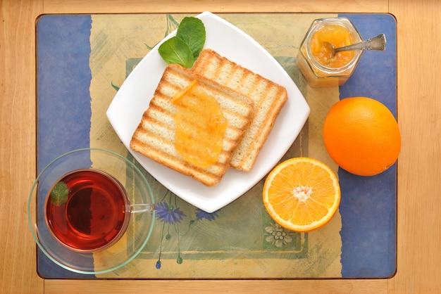 Broodtoast met sinaasappelmarmelade en zwarte thee met munt en sinaasappels