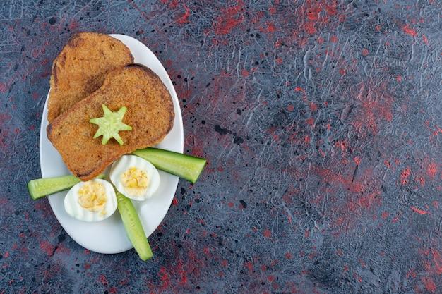 Broodtoost met gekookt ei en komkommers.