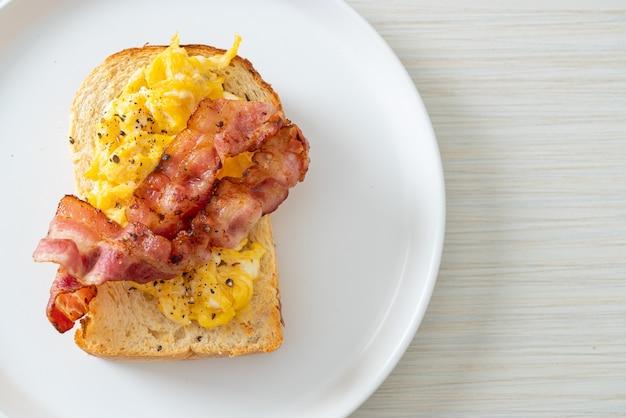 Broodtoost met roerei en spek op witte plaat Premium Foto
