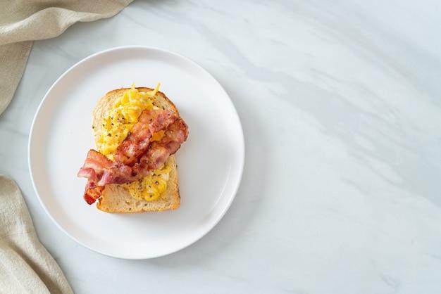 Broodtoost met roerei en spek op witte plaat