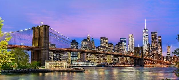 Brooklyn bridge en manhattan bij zonsondergang - new york, verenigde staten