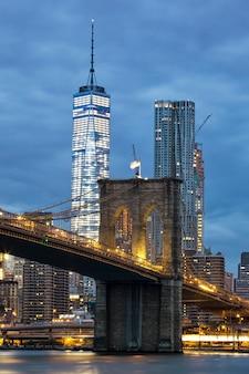 Brooklyn bridge in de schemering gezien vanuit het brooklyn bridge park in new york city.