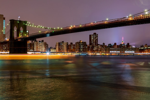 Brooklyn bridge in de schemering gezien vanuit new york city.
