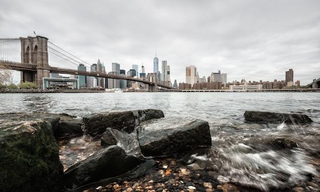 Brooklyn bridge met rotsen aan de oever van de east river