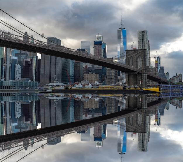 Brooklyn bridge op new york met weerspiegeling van wolkenkrabbers op de theems