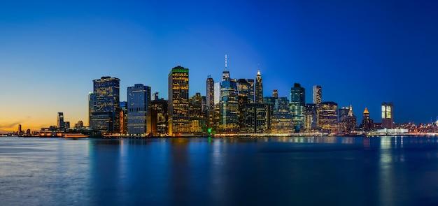Brooklyn bridge park met zonsondergang en de skyline van new york city
