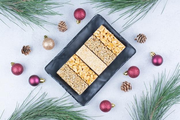 Brosse snoepjes op zwarte plaat met kerstversieringen.