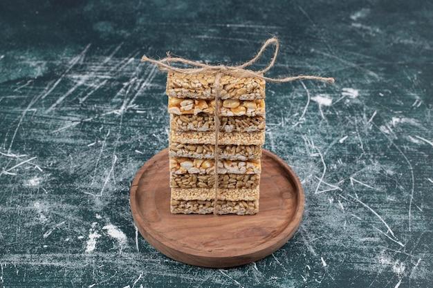 Brosse snoepjes vastgebonden met touw op houten plaat.