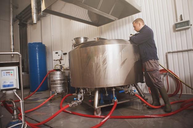 Brouwer die biergistingstank onderzoekt bij ambachtelijke bierfabriek