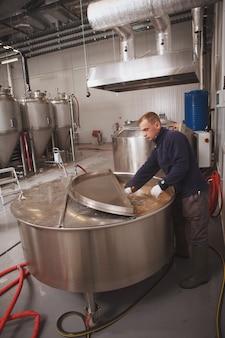 Brouwer die biertank onderzoekt tijdens fermentatieproces