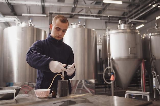 Brouwer die de kwaliteit van bier controleert in zijn bierfabriek, kopie ruimte