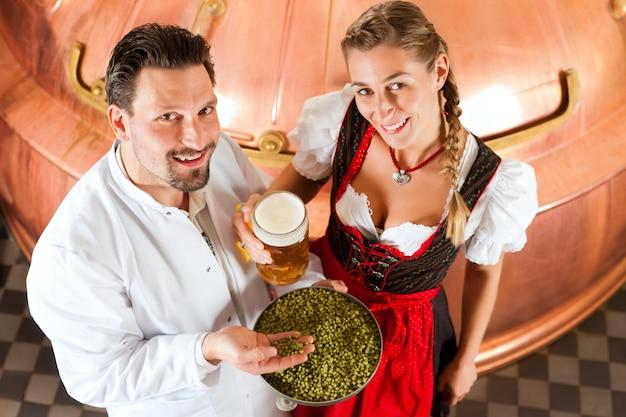 Brouwer en vrouw met bierglas in brouwerij