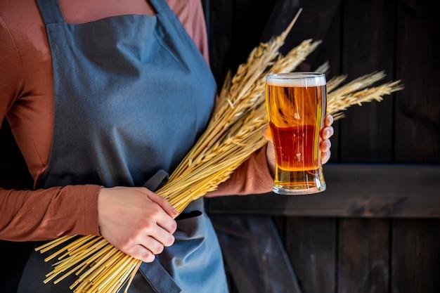 Brouwer in schort houdt glas bier en tarwe aartjes