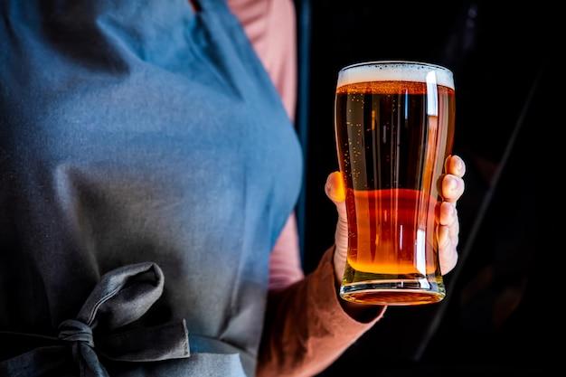 Brouwer in schort houdt glas bier