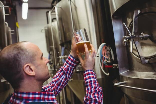 Brouwerijarbeider die bier in glas inspecteren