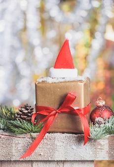 Brown gift pack met een rode strik en een kerstmuts