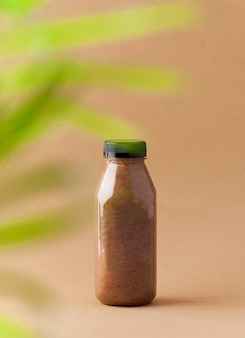 Brown smoothie fles op een beige achtergrond wit bladeren silhouet.