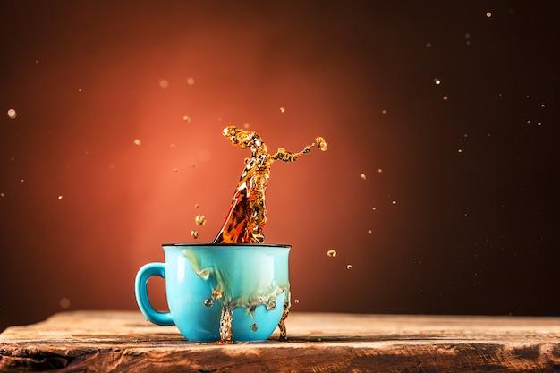 Brown spatten uit drinken uit kopje thee op een bruine achtergrond