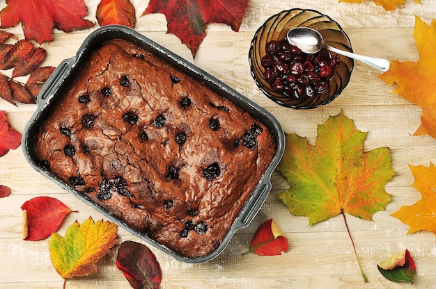 Brownie pie met kersen op een houten achtergrond met herfstbladeren - bovenaanzicht